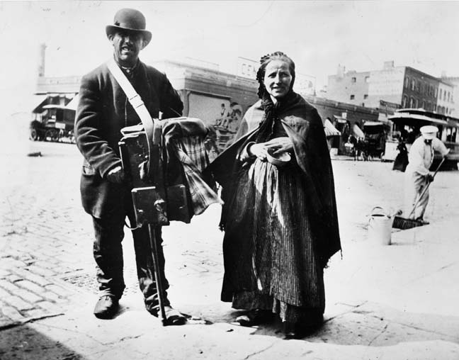 An organ grinder and his wife at 48th Street & 7th Avenue, New York. © Alice Austen